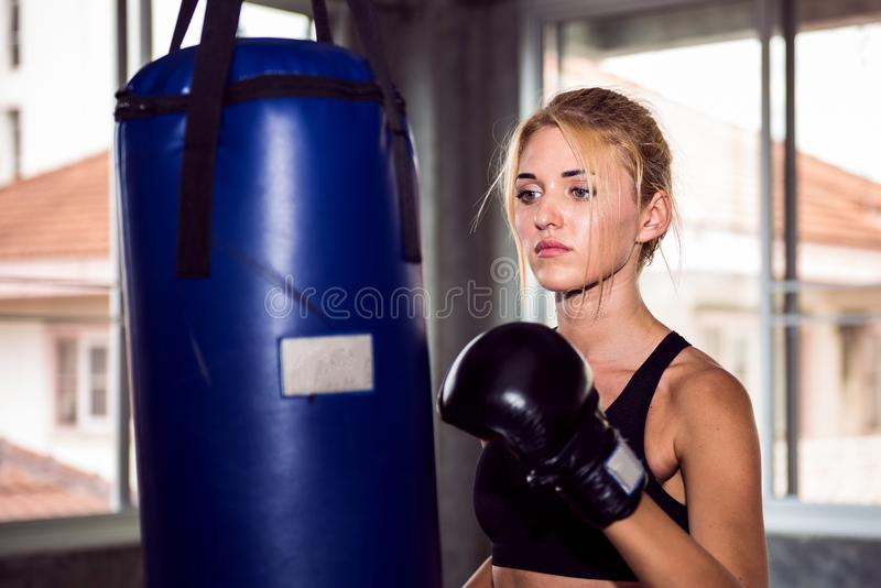 Young female punching a bag with boxing glove royalty free stock image