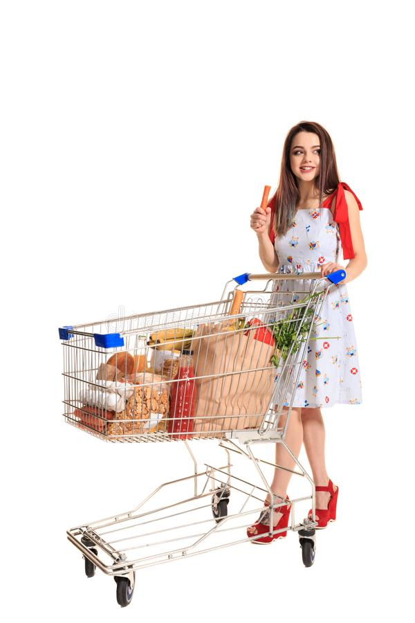A young female pushing a shopping cart full with groceries isolated on white background. Brunette in a summer dress makes purchases and gnaws raw carrots stock photography