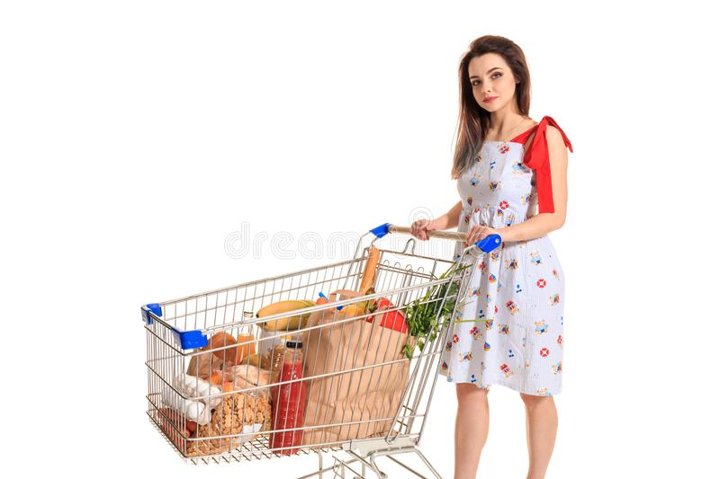 A young female pushing a shopping cart full with groceries isolated on white background. Brunette in a summer dress makes purchases royalty free stock image