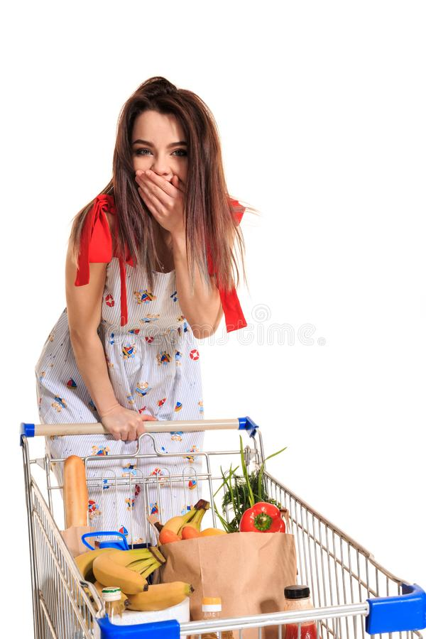 A young female pushing a shopping cart full with groceries isolated on white background. A woman laughs and closes her. A young female pushing a shopping cart stock photo