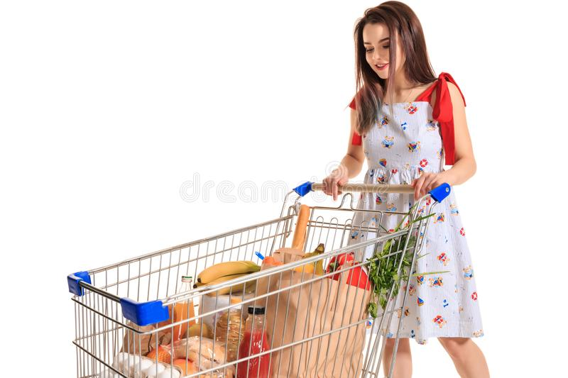 A young female pushing a shopping cart full with groceries isolated on white background. Brunette in a summer dress makes purchases royalty free stock photo