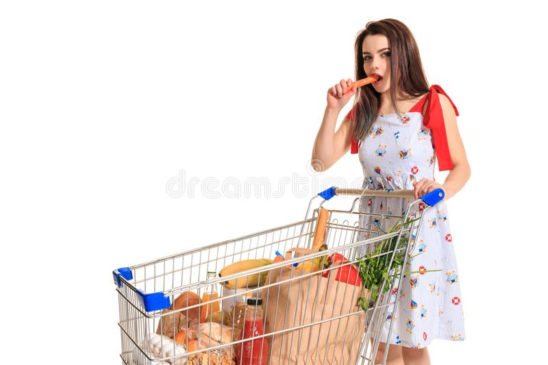 A young female pushing a shopping cart full with groceries isolated on white background. Brunette in a summer dress makes purchases and gnaws raw carrots royalty free stock photos