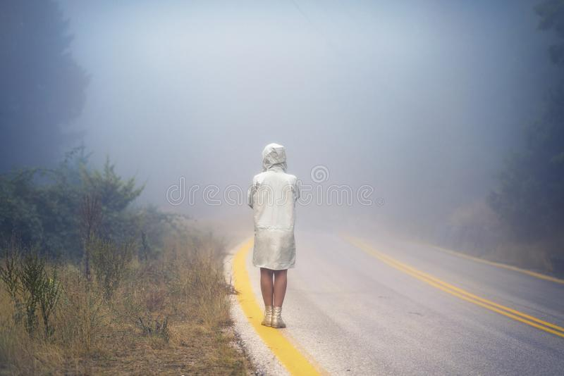 Young female in a raincoat on the road in the fog. Travel of women in the raincoat hitchhiking in the rain. Young female in a raincoat on the road in the fog stock image
