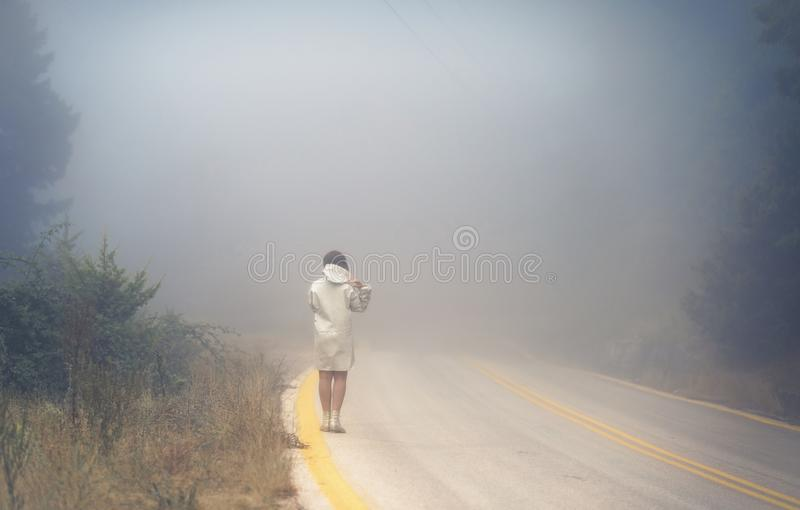 Young female in a raincoat on the road in the fog. Travel of women in the raincoat hitchhiking in the rain. Young female in a raincoat on the road in the fog royalty free stock images