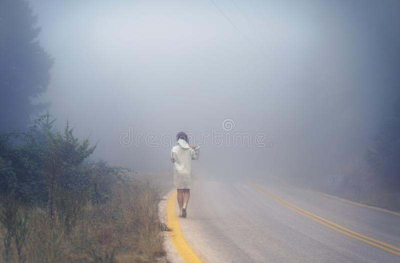 Young female in a raincoat on the road in the fog. Travel of women in the raincoat hitchhiking in the rain. Young female in a raincoat on the road in the fog royalty free stock photography