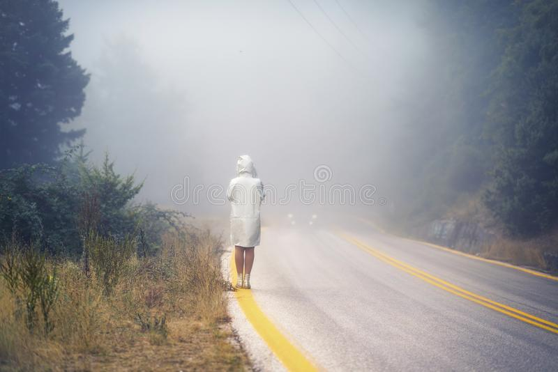 Young female in a raincoat on the road in the fog. Travel of women in the raincoat hitchhiking in the rain. Young female in a raincoat on the road in the fog royalty free stock image