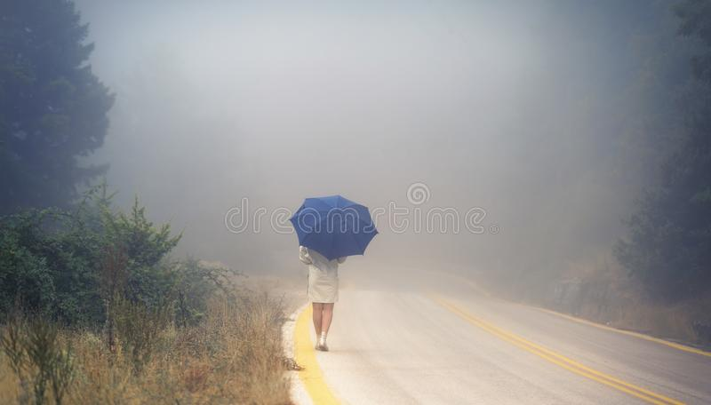 Young female in a raincoat and umbrella on the road in the fog. Travel of women in the raincoat hitchhiking in the rain. Young female in a raincoat and umbrella royalty free stock photography