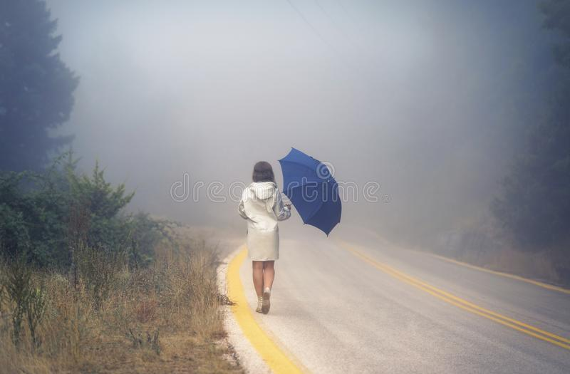 Young female in a raincoat and umbrella on the road in the fog. Travel of women in the raincoat hitchhiking in the rain. Young female in a raincoat and umbrella stock images