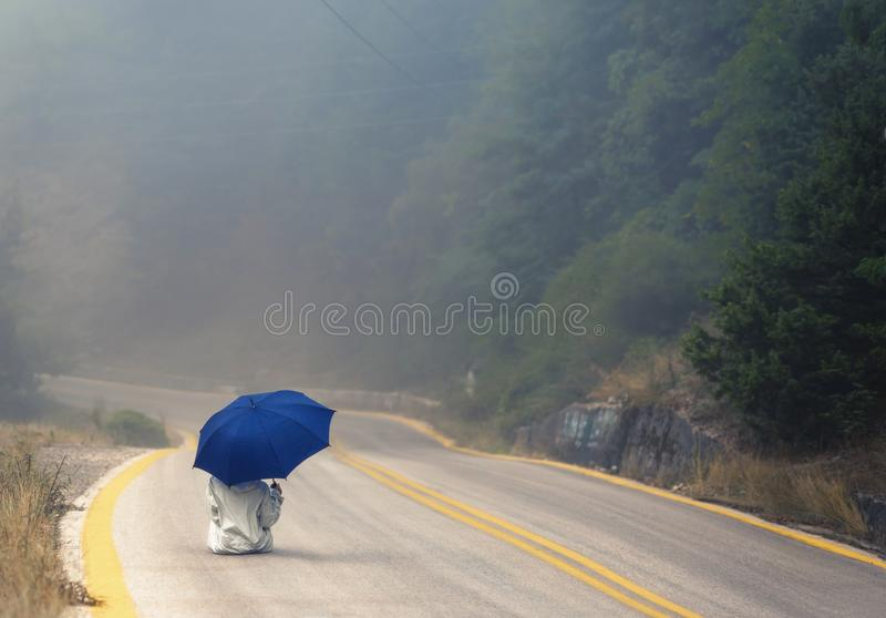 Young female in a raincoat and umbrella on the road in the fog. Travel of women in the raincoat hitchhiking in the rain. Young female in a raincoat and umbrella stock photo