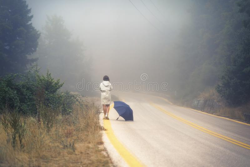 Young female in a raincoat and umbrella on the road in the fog. Travel of women in the raincoat hitchhiking in the rain. Young female in a raincoat and umbrella royalty free stock image
