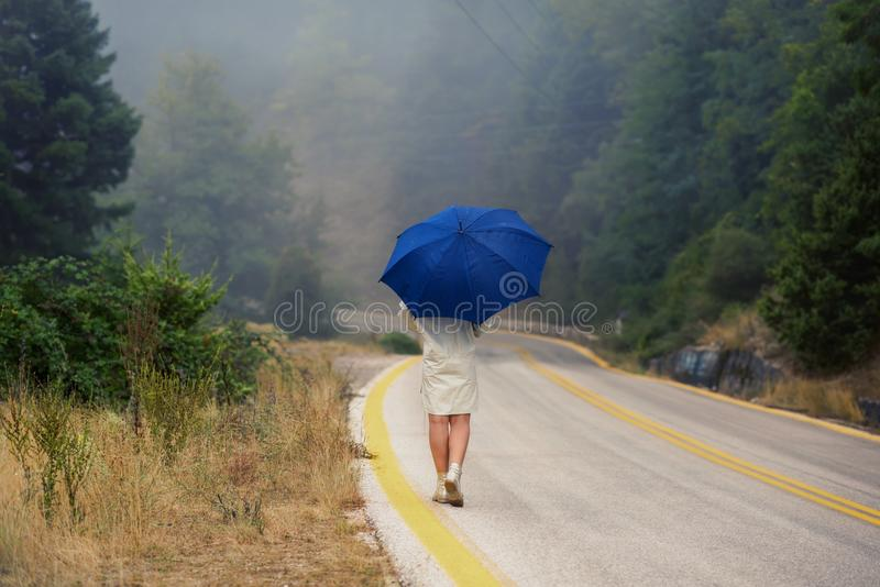 Young female in a raincoat and umbrella on the road in the fog. Travel of women in the raincoat hitchhiking in the rain. Young female in a raincoat and umbrella royalty free stock photo