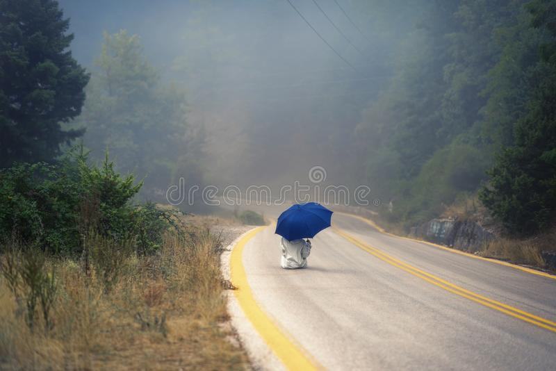 Young female in a raincoat and umbrella on the road in the fog. Travel of women in the raincoat hitchhiking in the rain. Young female in a raincoat and umbrella royalty free stock images