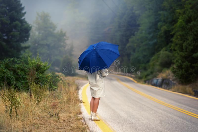 Young female in a raincoat and umbrella on the road in the fog. Travel of women in the raincoat hitchhiking in the rain. Young female in a raincoat and umbrella royalty free stock photos