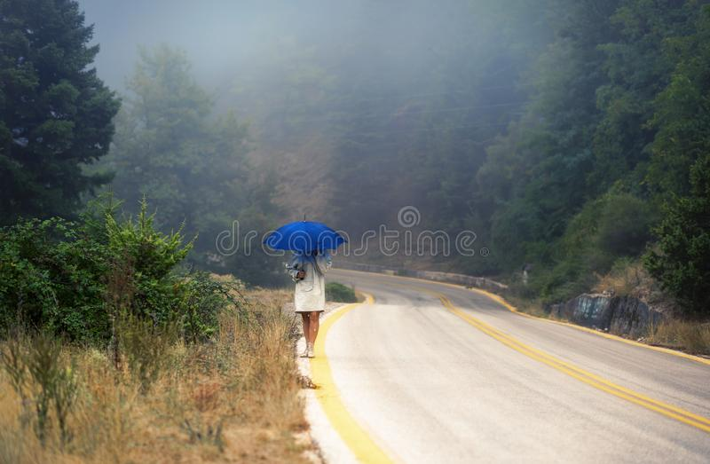 Young female in a raincoat and umbrella on the road in the fog. Travel of women in the raincoat hitchhiking in the rain. Young female in a raincoat and umbrella stock image