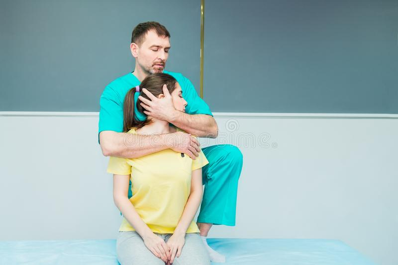 Young female receiving massage from therapist. A chiropractor stretching his patient`s neck in medical office. Neurological physi stock image