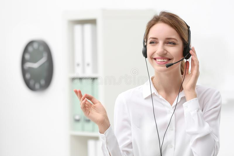 Young female receptionist with headset. In office royalty free stock images