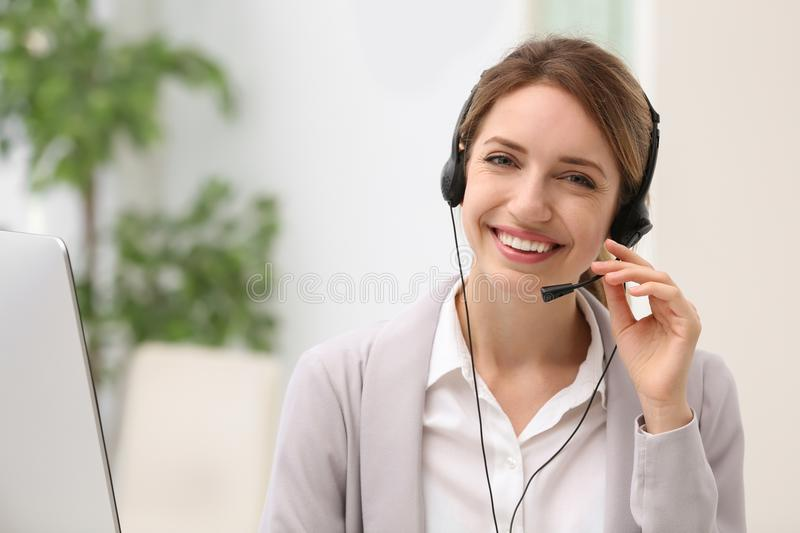 Young female receptionist with headset. In office stock photos