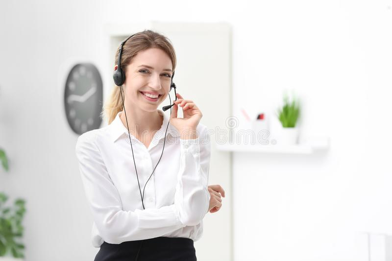 Young female receptionist with headset. In office royalty free stock photo