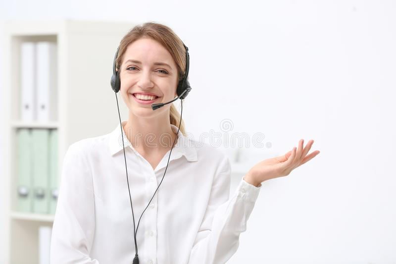 Young female receptionist with headset. In office royalty free stock image