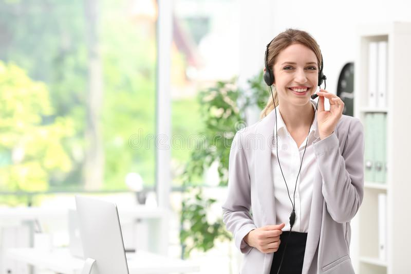 Young female receptionist with headset. In office royalty free stock photos
