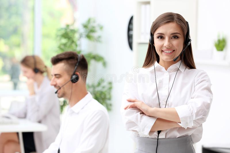 Young female receptionist with headset. In office stock photography