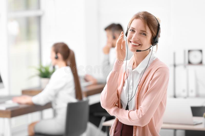 Young female receptionist with headset. In office royalty free stock photography
