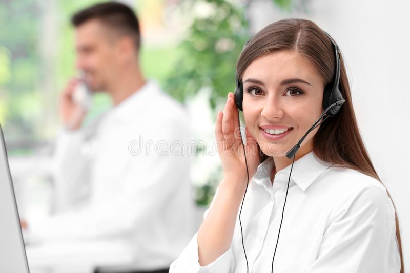 Young female receptionist with headset. In office stock photo