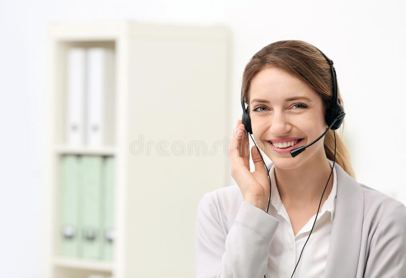 Young female receptionist with headset in office. Young smiling female receptionist with headset in office royalty free stock image