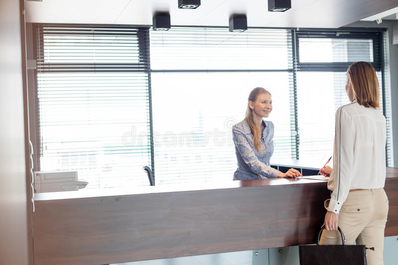 Young female receptionist looking at businesswoman signing document in office.  stock photo