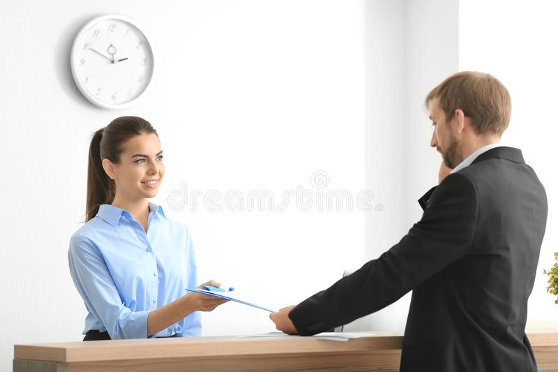 Young female receptionist meeting client. In office stock photo