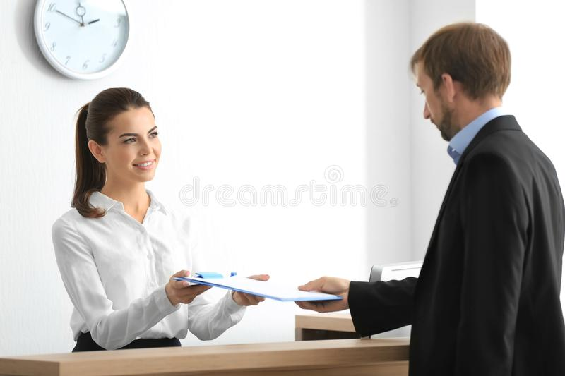 Young female receptionist meeting client. In office stock photography