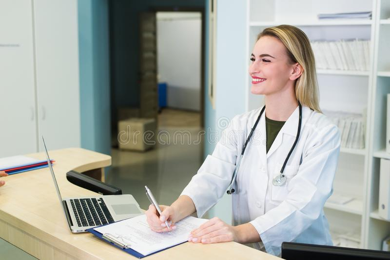 Young female receptionist talkingto the client patient in hospital.  royalty free stock images