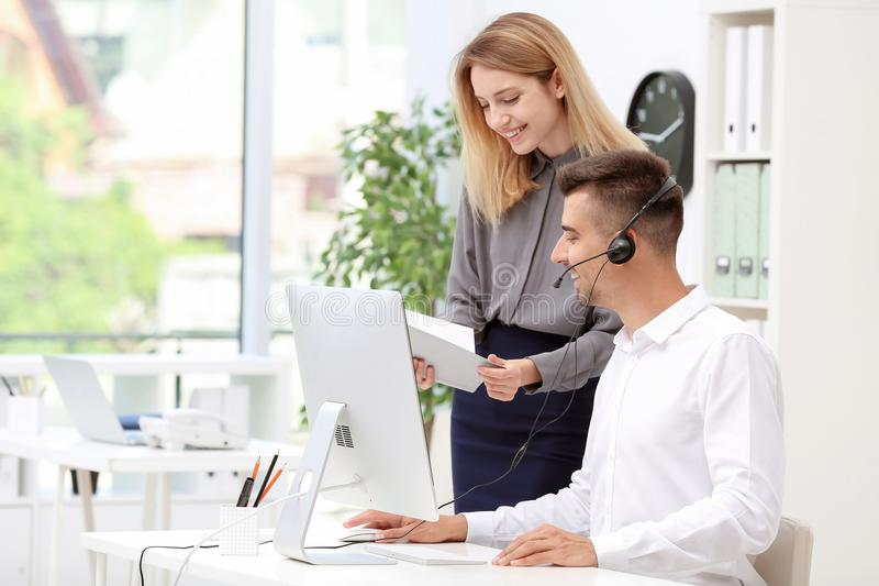 Young female receptionist with trainee. At workplace royalty free stock image