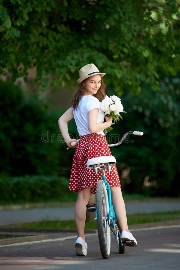 Young female in red skirt riding blue bicycle with flowers in her hands down green paved city street royalty free stock images