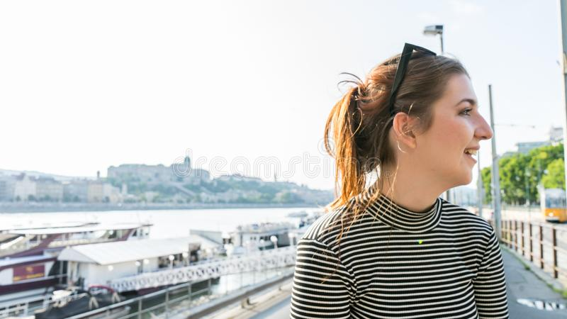 Young female redhead girl feeling happy in the side of the danube. Pretty caucasian woman outside in Budapest, smiling in the royalty free stock photo