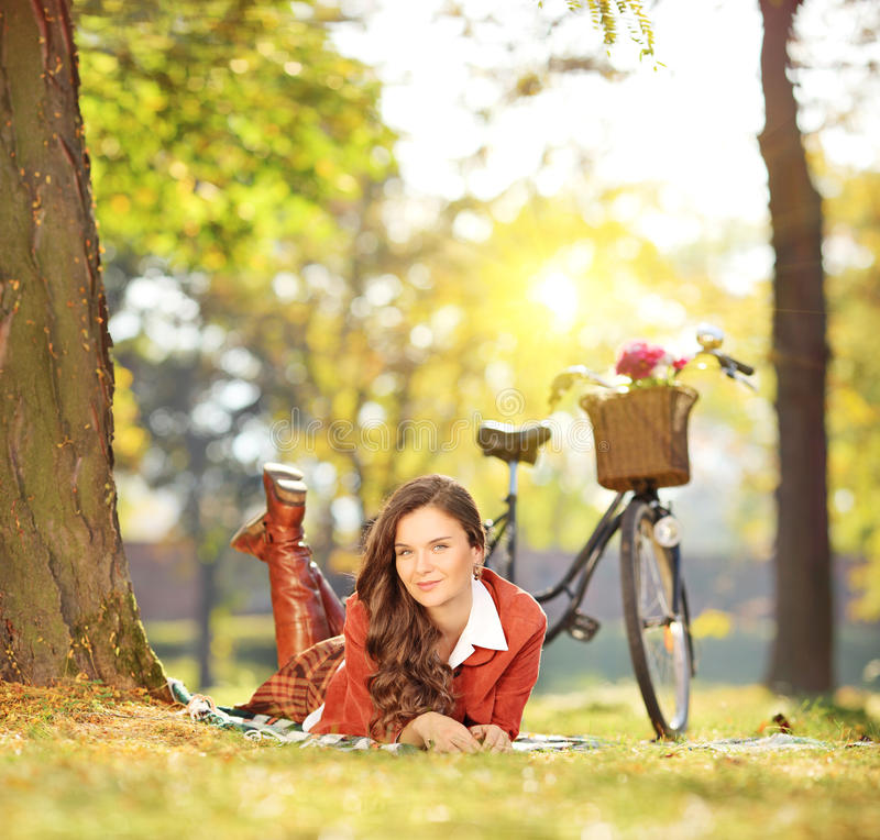 Young female relaxing on a grass with bicycle in a park on a sun royalty free stock images