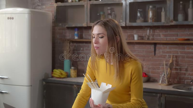 Young female relish asian lunch from white box. Woman eating chinese food to go. Lady enjoy dish at home use laptop. Adult businesswoman eats and working at the royalty free stock photography