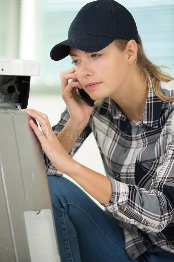 Young female repairer on phone fixing printer. Young female repairer on the phone fixing printer royalty free stock photo