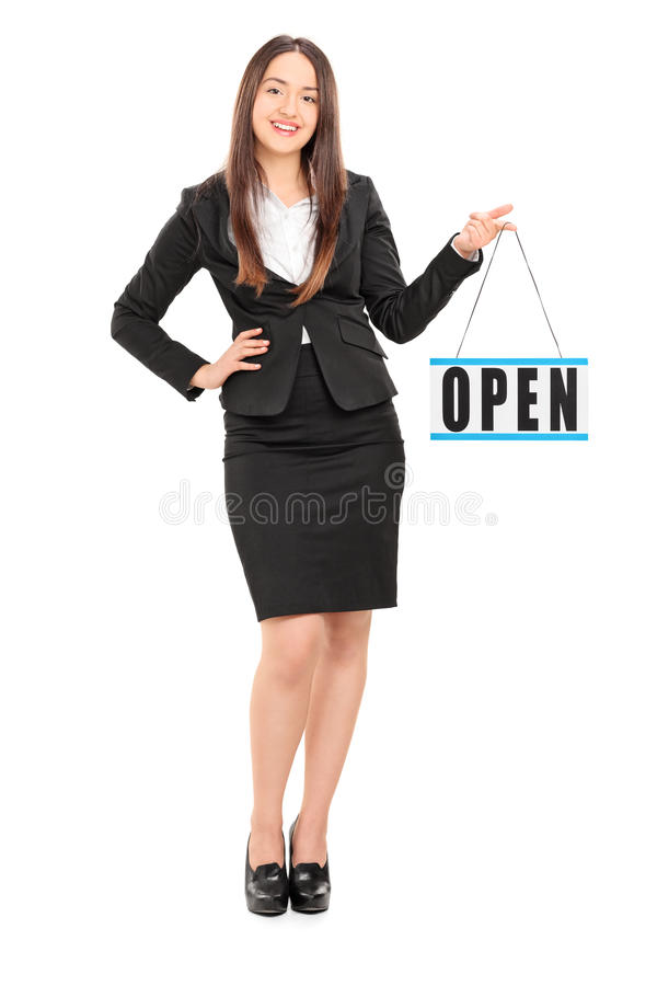 Young female retailer holding an open sign. Full length portrait of a young female retailer holding an open sign isolated on white background stock photo
