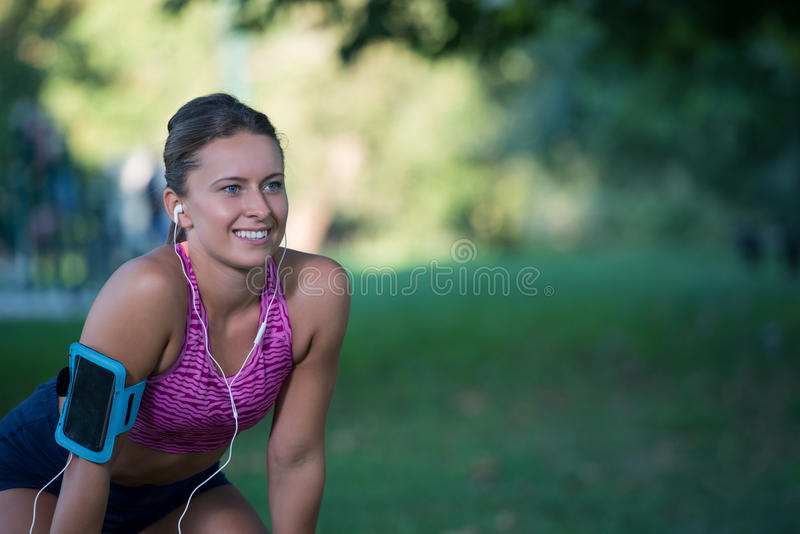 Young female runner is having break and listening to music during the run in city on a quay stock image