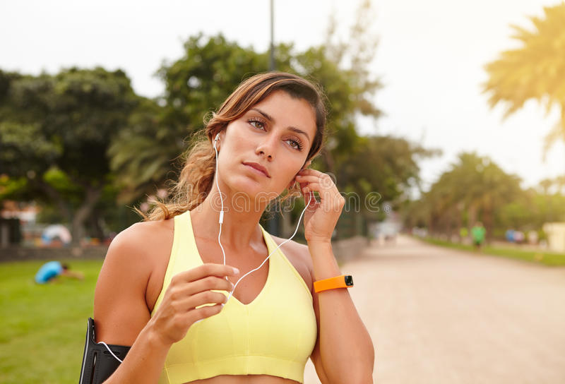 Young female runner listening to music outdoors royalty free stock image