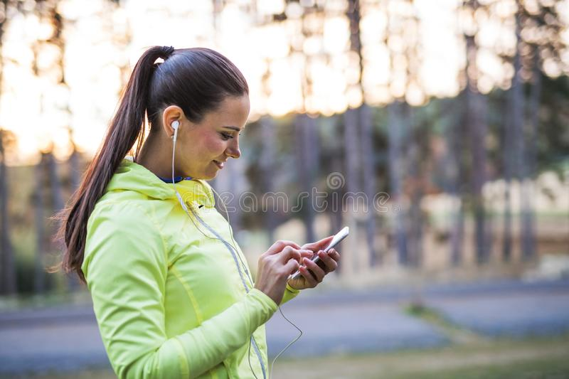 A young female runner outdoors in autumn nature, using smartphone. stock photo