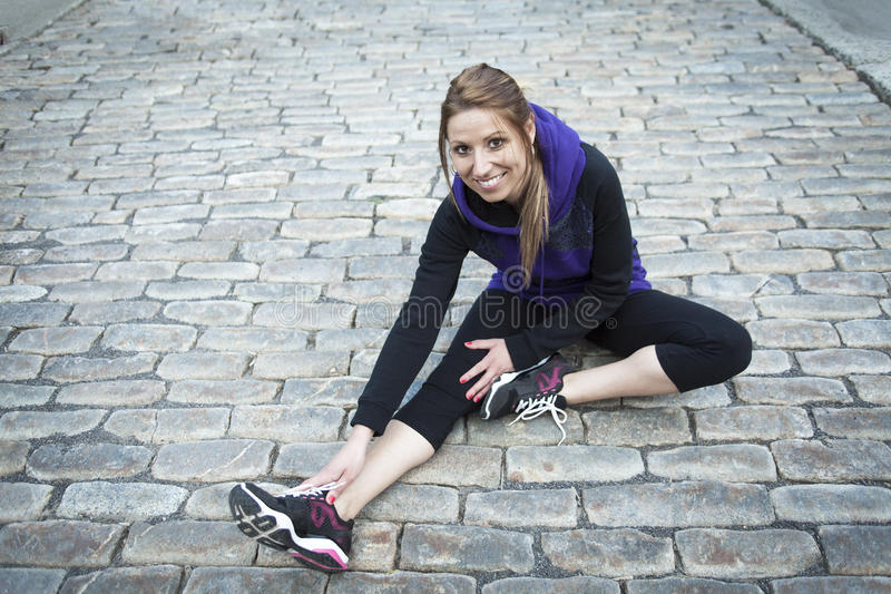 Young female runner sitting on tiled pavement in. A Young female runner sitting on tiled pavement in old city center stock image