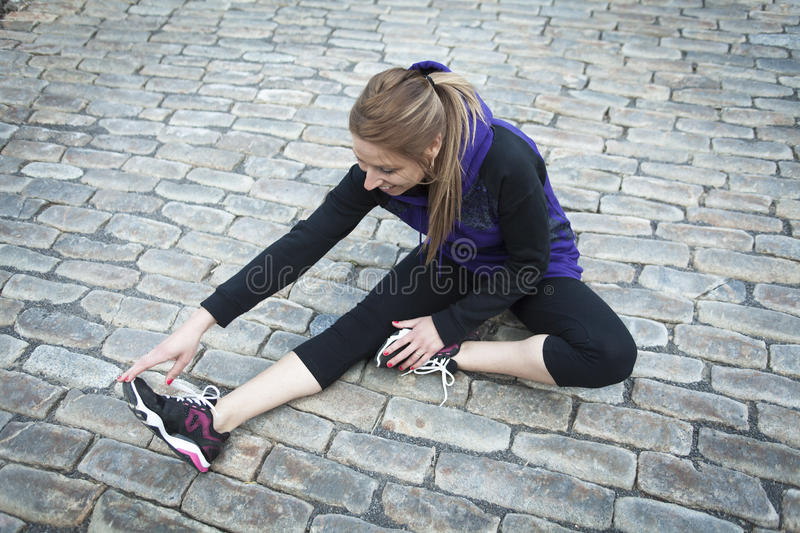 Young female runner sitting on tiled pavement in. A Young female runner sitting on tiled pavement in old city center royalty free stock images