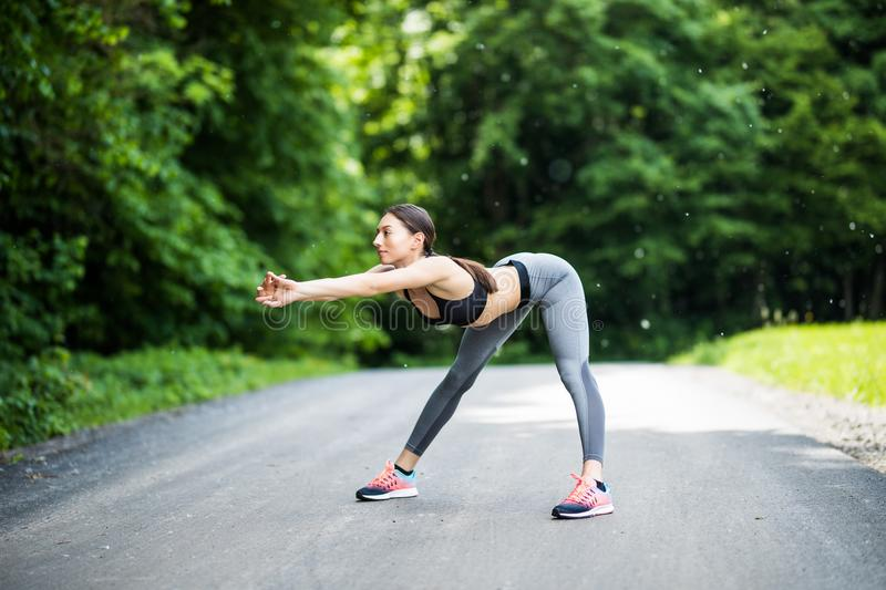 Young female runner stretching arms before running. Woman warming before workout in the park royalty free stock image