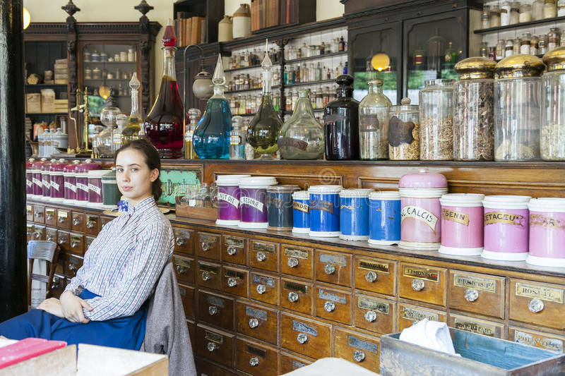 Young female sales assistant sitting down in Victorian Chemist/ stock images