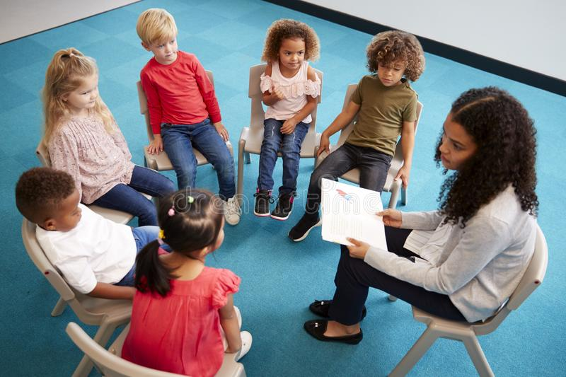 Young female school teacher reading a book to infant school children, sitting on chairs in a circle in the classroom listening, el. Evated view royalty free stock photo
