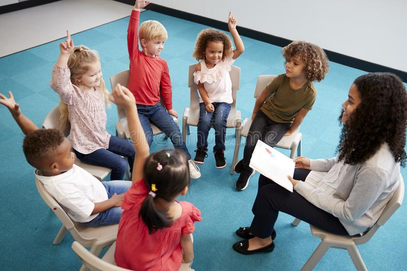 Young female school teacher reading a book to infant school children, sitting on chairs in a circle in the classroom raising hands. To answer a question royalty free stock image