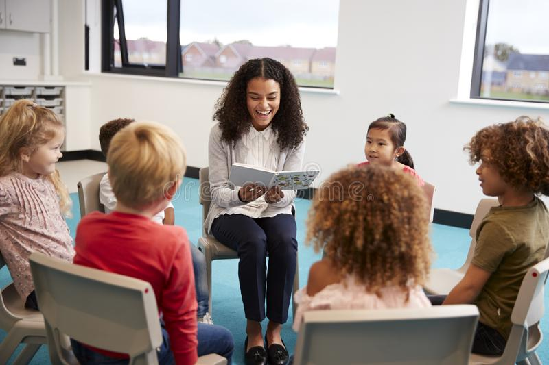 Young female school teacher reading a book to kindergarten children, sitting on chairs in a circle in the classroom listening royalty free stock images
