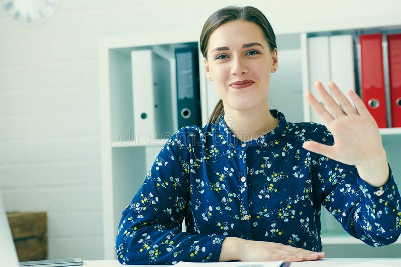 Front view of beautiful young businesswoman says hello with hand. stock photos
